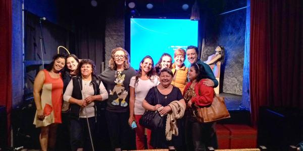 Grupo de atores com pessoas com deficiência e audiodescritores, logo após a peça.