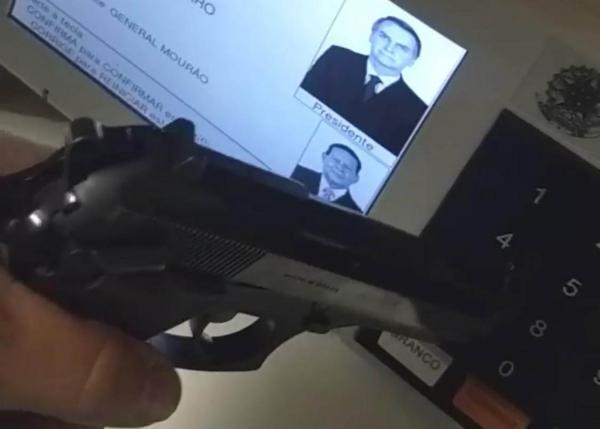 Eleitor exibe arma na urna no domingo