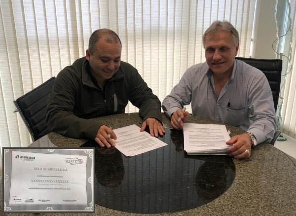Os presidentes F\u00e1bio Aguayo e Luis Alberto ao assinar o acordo de reajuste da categoria e a cria\u00e7\u00e3o do Selo Gorjeta Legal