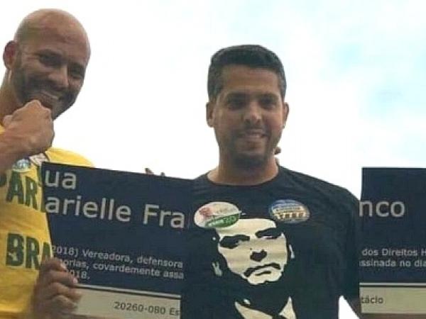 Rodrigo Amorim (à direita) sorri ao exibir placa destruída em homenagem a Marielle