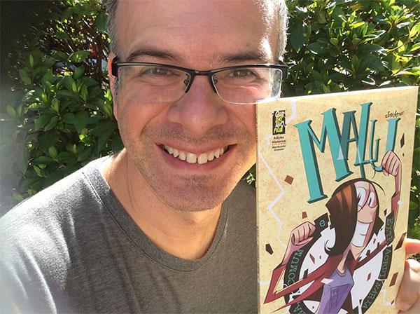 O escritor  curitibano  José Aguiar  com o livro 'Malu: pequena, comum e extraordinária'